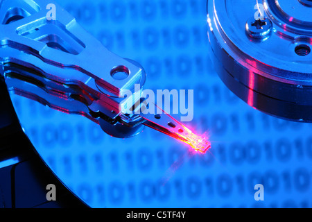 Computer hard drive, opened, writing/reading head and hard disk. Binary code numbers are reflecting on the hard - Stock Photo
