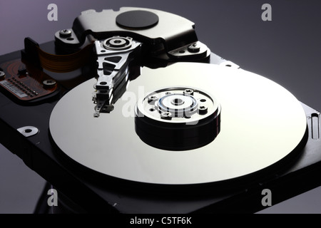 Computer hard drive, opened, reading/writing head and hard disk. - Stock Photo