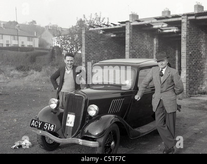 Two men standing proudly alongside a Ford Popular in the 1950's. - Stock Photo