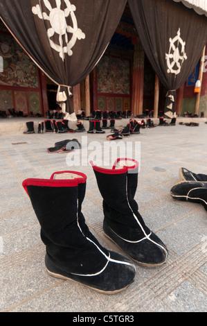 Foot wear belonging to Tibetan Buddhist monks outside temple, Longwu Monastery, Tongren, Qinghai Province, China - Stock Photo