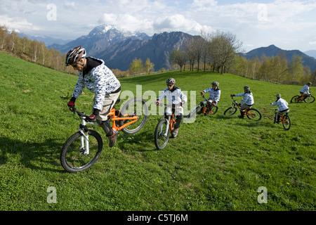 Italy, Lake Como, Group of mountain bikers riding across meadow - Stock Photo