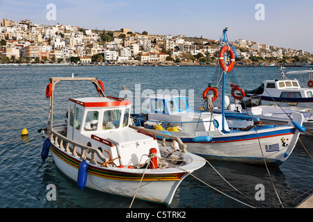 Greece, Crete, Sitia, Fishing boats moored at harbour and town in background - Stock Photo