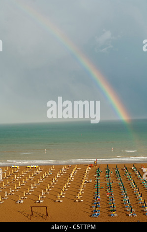 Italy, Lignano Beach with sunloungers, rainbow in background - Stock Photo