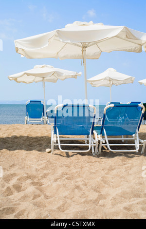 Greece, Sun Loungers and sunshades on beach - Stock Photo
