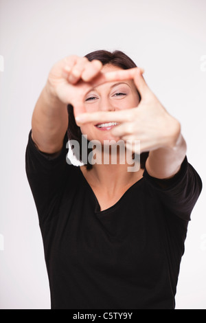 Mid adult woman showing hand sign against white background, smiling, portrait - Stock Photo