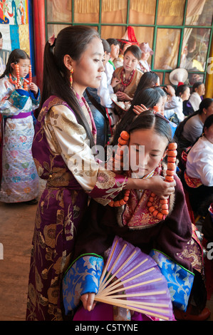 Young girl wearing heavy coral jewelry waits to perform at shaman harvest festival, Tongren, Qinghai Province, China - Stock Photo
