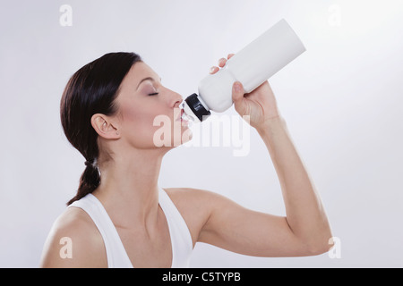 Mid adult woman drinking from water bottle against white background - Stock Photo
