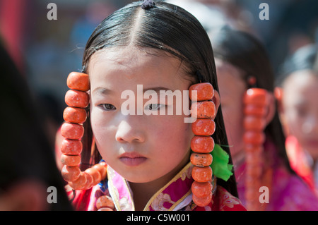 Young girls wearing heavy coral jewelry perform at shaman harvest festival, Tongren, Qinghai Province, China - Stock Photo