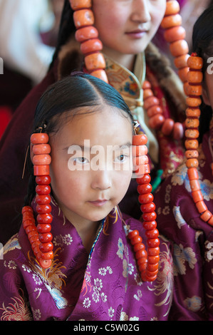 Young girls wearing heavy coral jewelry wait to perform at shaman harvest festival, Tongren, Qinghai Province, China - Stock Photo