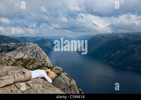Tourist standing on the edge of Preikestolen or Pulpit Rock, Lysefjord. - Stock Photo