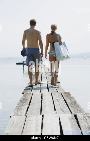 Germany, Bavaria, Young couple wearing swimwear walking on jetty, rear view - Stock Photo