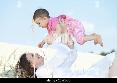 Germany, Bavaria, Mother lying and holding aloft baby girl - Stock Photo