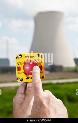 Germany, Bavaria, Unterahrain, Hand of man pressing shut off button near AKW Isar - Stock Photo