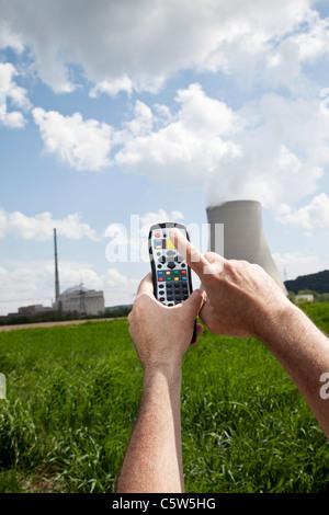 Germany, Bavaria, Unterahrain, Hand of man using remote control near AKW Isar - Stock Photo