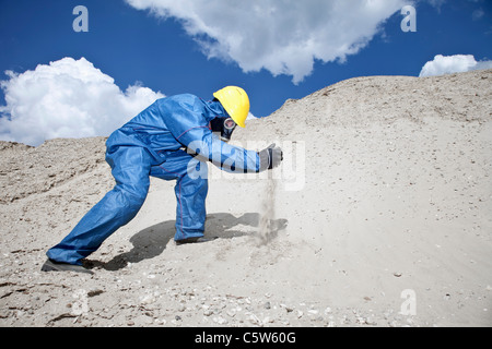 Germany, Bavaria, Man in protective wear spilling sand on sand dune - Stock Photo