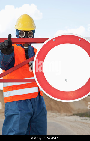 Germany, Man in protective workwear near stop sign - Stock Photo
