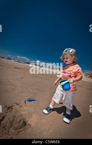 a little boy makes sandcastles on a sandy beach on a cloudless summers day - Stock Photo