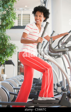 Germany, Bavaria, Woman on crosstrainer, smiling - Stock Photo