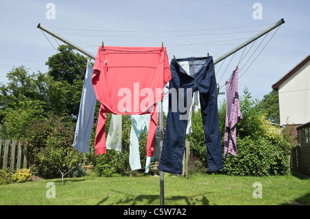 Wet clothes hanging out on a rotary washing line to dry outdoors in a garden on a warm sunny day. UK, Britain. - Stock Photo