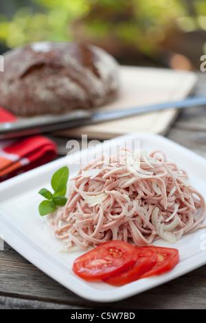 Sausage salad on platter, close-up - Stock Photo