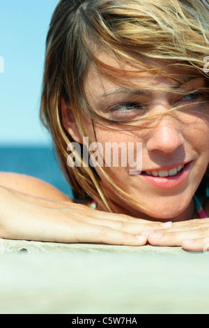 Italy, Sardinia, Young woman on beach, portrait, close-up - Stock Photo
