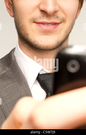 Businessman holding mobile phone against white background, smiling, close up - Stock Photo