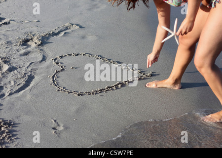 Italy, Sardinia, Person drawing heart in sand - Stock Photo