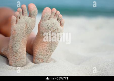 Italy, Sardinia, Person lying on beach, sandy feet - Stock Photo