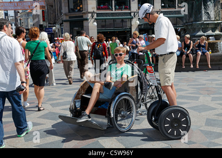 Idle bicycle taxi driver and Segway Tour guide relaxing among tourists on Strøget in Copenhagen on a warm and sunny - Stock Photo