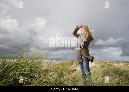Germany, Schleswig Holstein, Amrum, Woman Looking out to Sea - Stock Photo