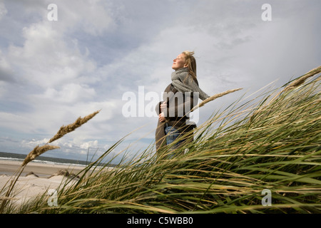 Germany, Schleswig Holstein, Amrum, Young woman on grassy sand dune - Stock Photo