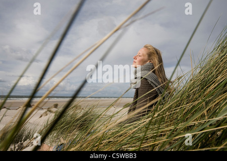 Germany, Schleswig Holstein, Amrum, Young woman on grassy sand dune, eyes closed - Stock Photo
