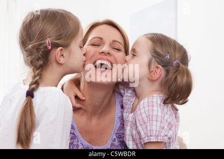 Germany, Munich, Girls (4-7) kissing on mother's cheek - Stock Photo