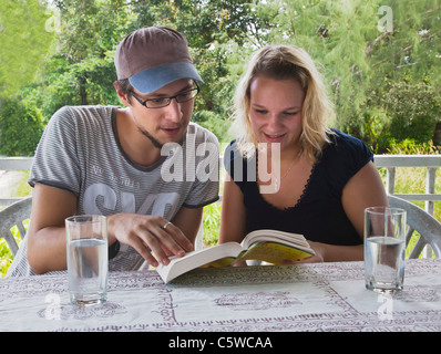 Volunteers do some homework during a home stay at Ben Lion on KOH PHRA THONG ISLAND - THAILAND - Stock Photo
