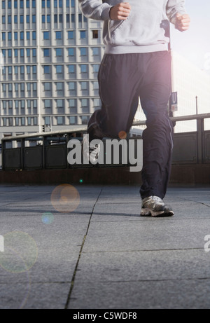 Germany, Berlin, Person jogging on street, skyscrapers in background, low section - Stock Photo