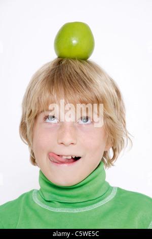 Little boy (10-11) balancing apple on head - Stock Photo