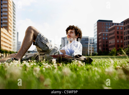 Germany, Berlin, Man relaxing on lawn, in background high rise buildings - Stock Photo