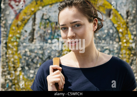 Germany, Berlin, Young woman standing in front of wall with graffiti, portrait, close-up - Stock Photo