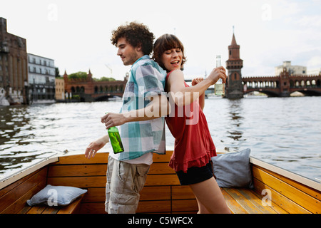 Germany, Berlin, Young couple on motorboat, holding bottles, standing back to back - Stock Photo
