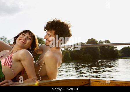 Germany, Berlin, Young couple on motor boat, man wearing headphones, portrait, close-up - Stock Photo