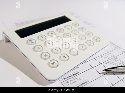 Close up of calculator and pen on form - Stock Photo