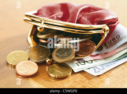 Close up of euro notes and purse spilling coins - Stock Photo