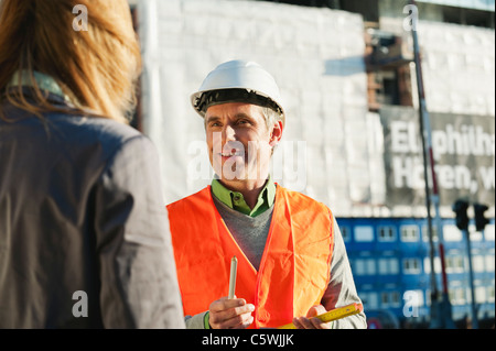 Germany, Hamburg, Man and woman standing at harbour - Stock Photo