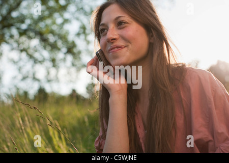 Germany, Berlin, Teenage girl using mobile phone, smiling - Stock Photo