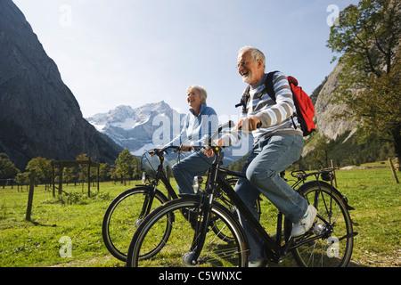 Austria, Karwendel, Senior couple biking - Stock Photo