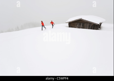 Italy, South Tyrol, Couple cross-country skiing next to cabin - Stock Photo