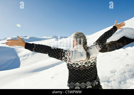 Italy, South Tyrol, Seiseralm, Senior woman, arms outstretched, rear view - Stock Photo
