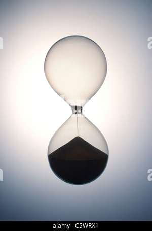 Hour glass running out of time and sand - Stock Photo