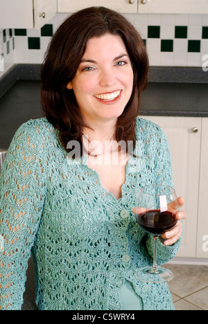 Beautiful Young Woman Wearing A Blue Crochet Sweater Relaxing At Home With A Glass Of Wine - Stock Photo