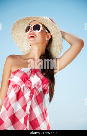 smiling female against blue sky - Stock Photo
